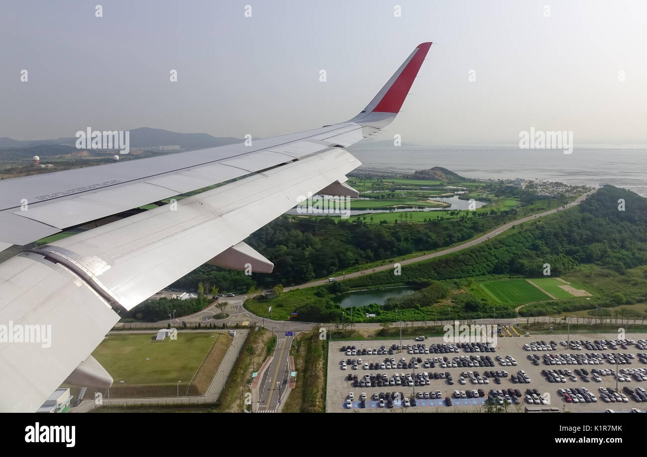 Wing Of Airplane With Green Island Background View From Window