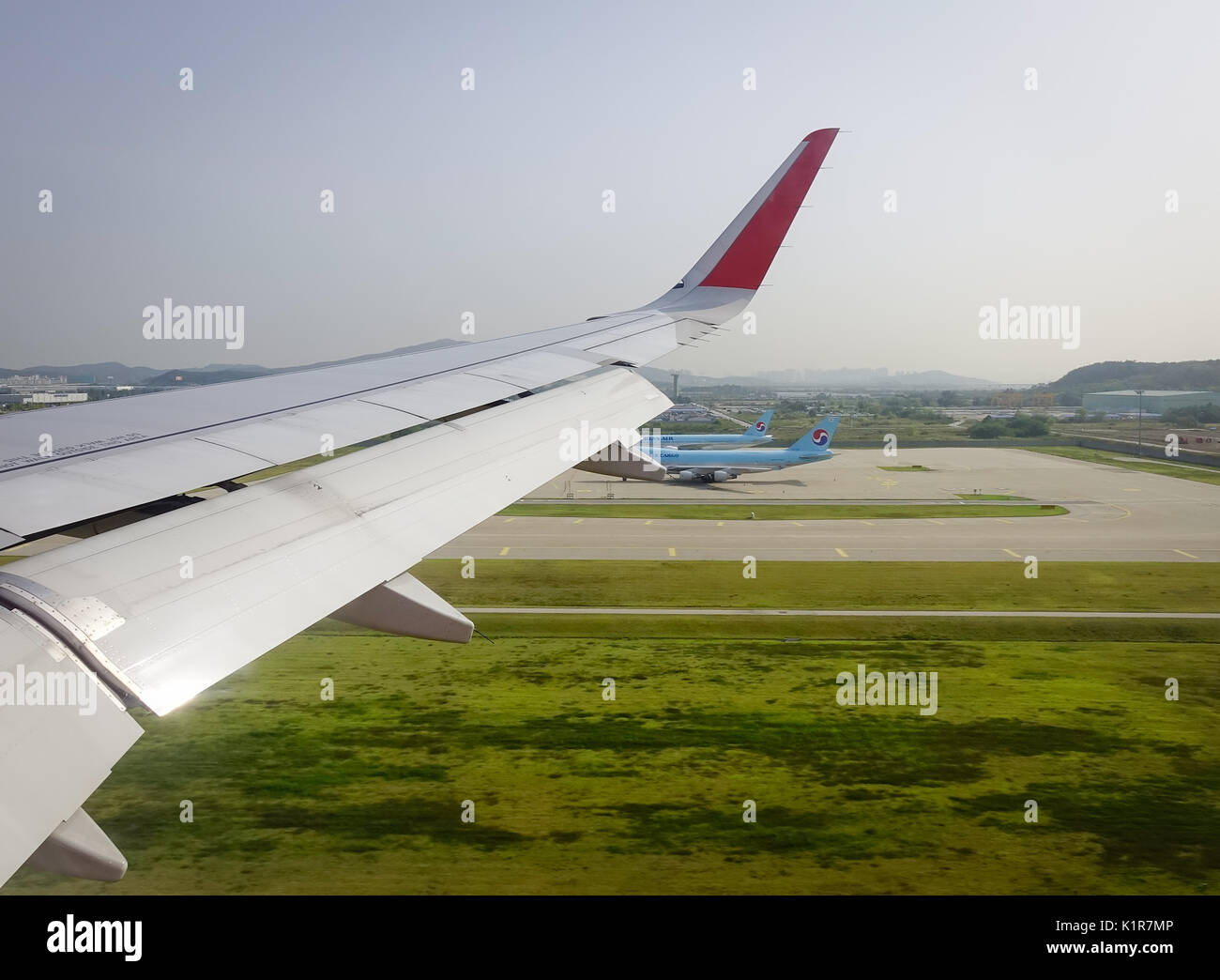 Wing Of Airplane With The Runway Background View From Window Seat