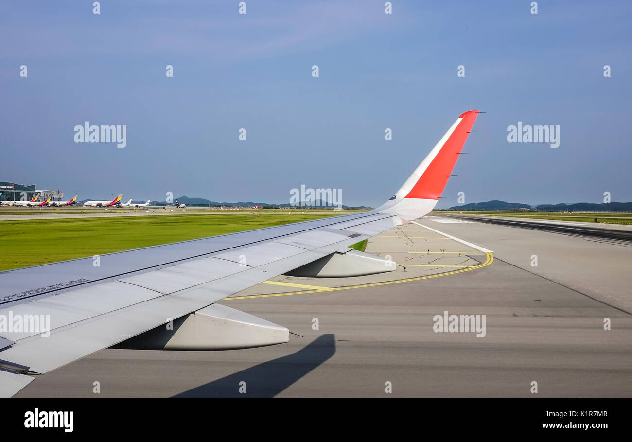 Wing Of Airplane With The Runway Background At Sunny Day View