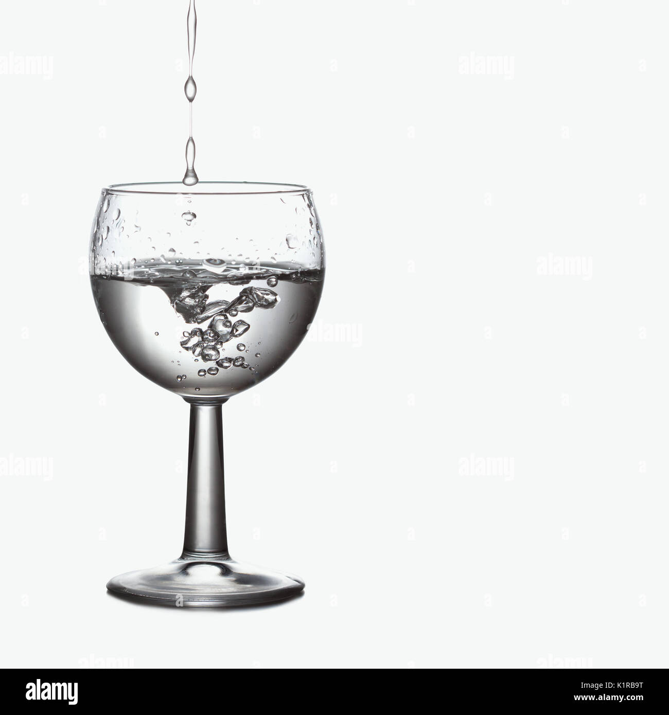 Pour, splash in natural clear water glass. relax spa ecologiac concept. Frozen motion. soft focus, macro view, white background - Stock Image