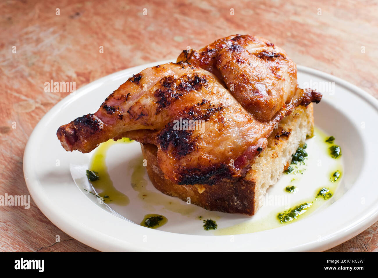 Natural organic Grilled chicken leg on bread close-up. white plate background - Stock Image