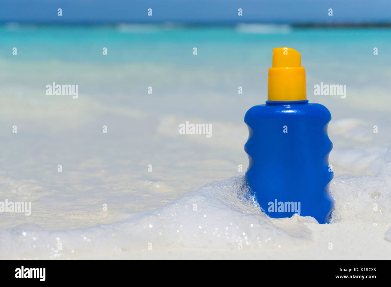 Bottle of sun lotion suncream protection on a tropical beach - Stock Image
