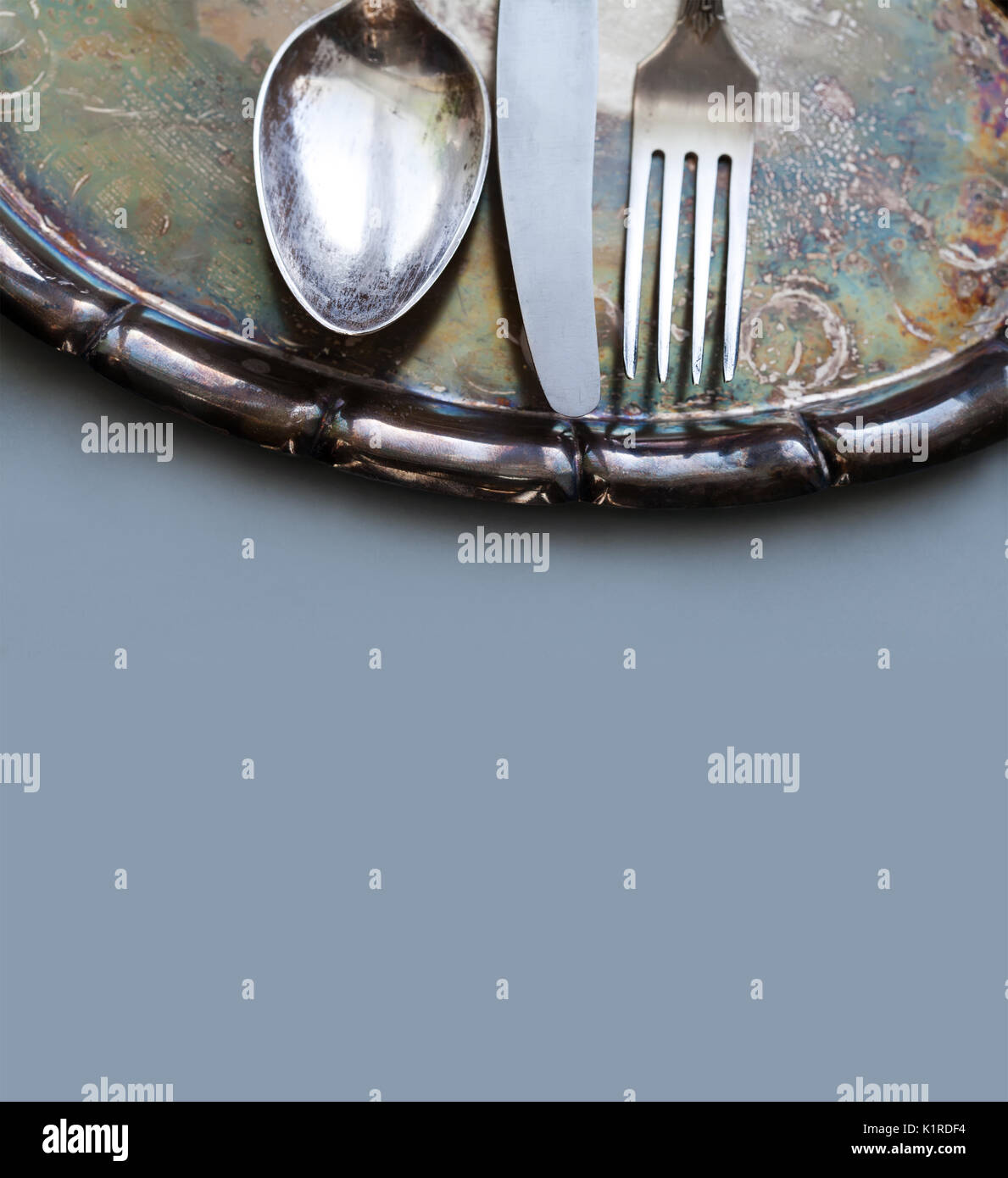 Kitchen tableware set on the vintage silver tray. spoon, knife and fork. gray paper background. Soft focus. - Stock Image
