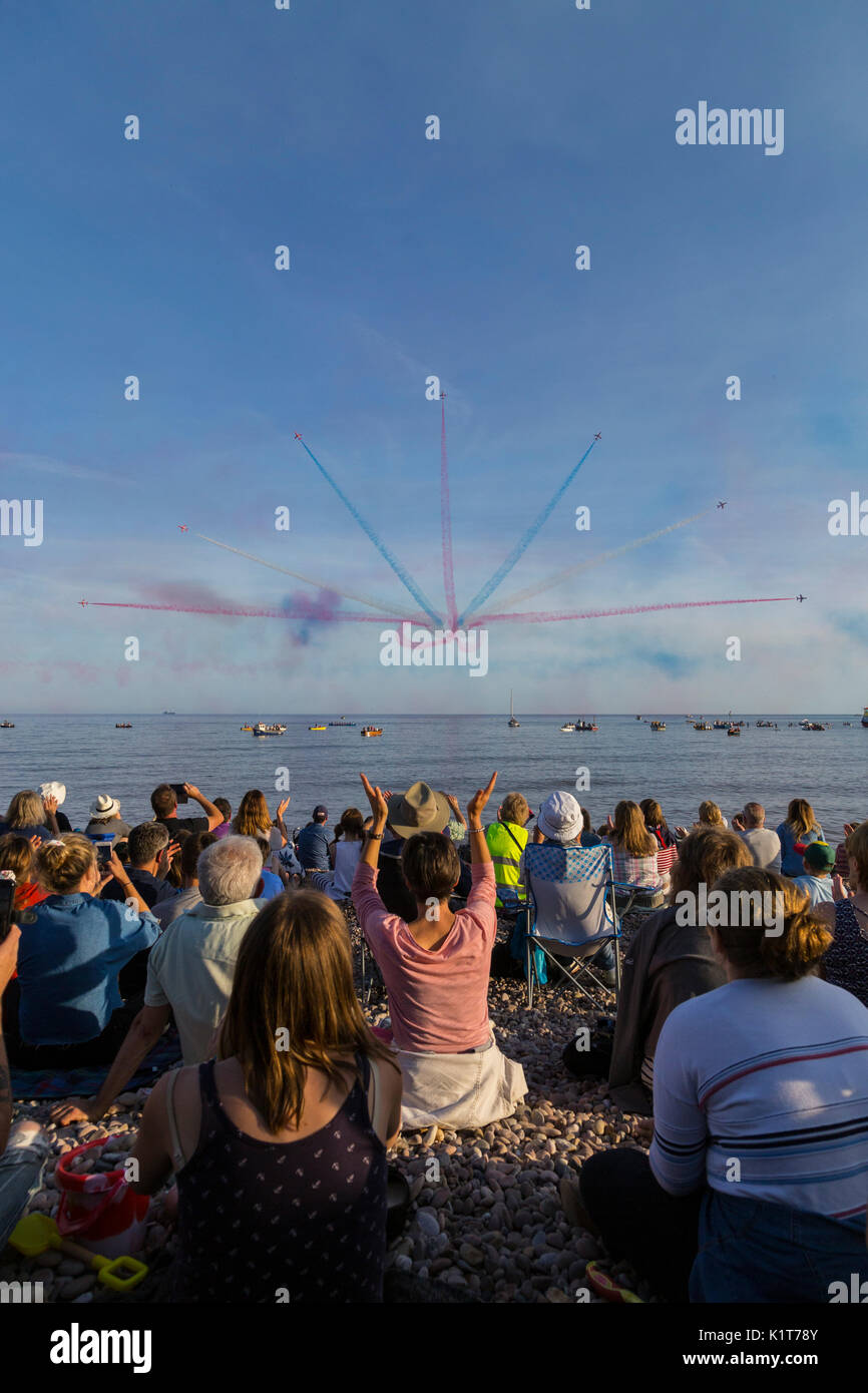 Crowds applaud on Sidmouth beach as the Red Arrows perform overhead during the town's Regatta weekend. - Stock Image