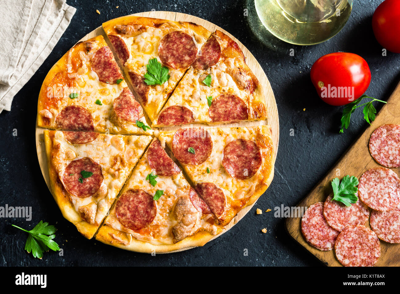 Pepperoni Pizza with ingredients - Fresh homemade pizza with pepperoni, cheese and tomato sauce and ingredients on rustic black stone background with  - Stock Image