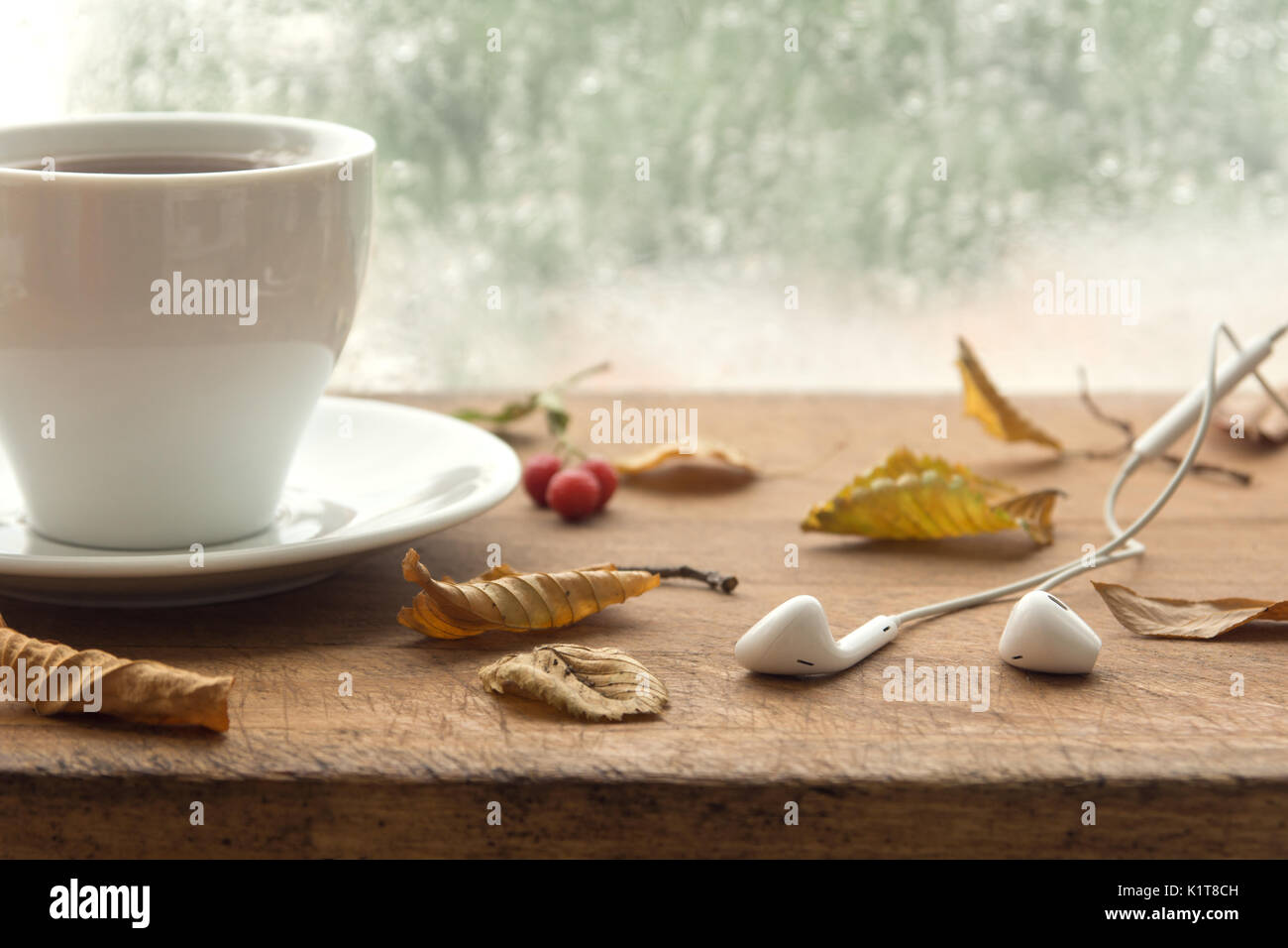 Cup of coffee or tea and earbuds with autumn leaves near a window. Autumn playlist concept. Autumn music for rainy days. - Stock Image