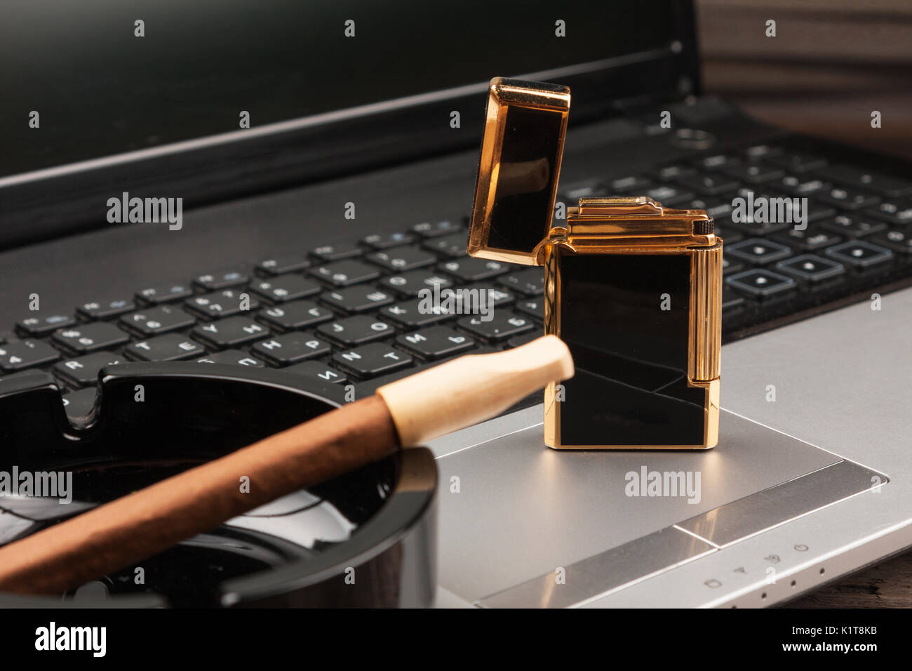 Luxurious gold lighter and cigar on laptop background. As a background. splash screen Stock Photo