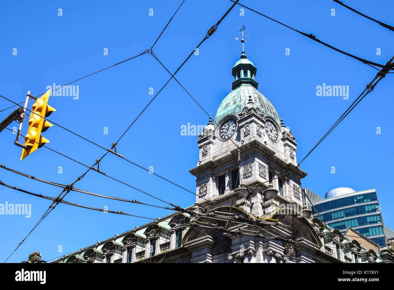 Old main post office building, now part of a shopping mall, and electrical overhead lines for public trolley busses and trams in downtown Vancouver, C - Stock Image