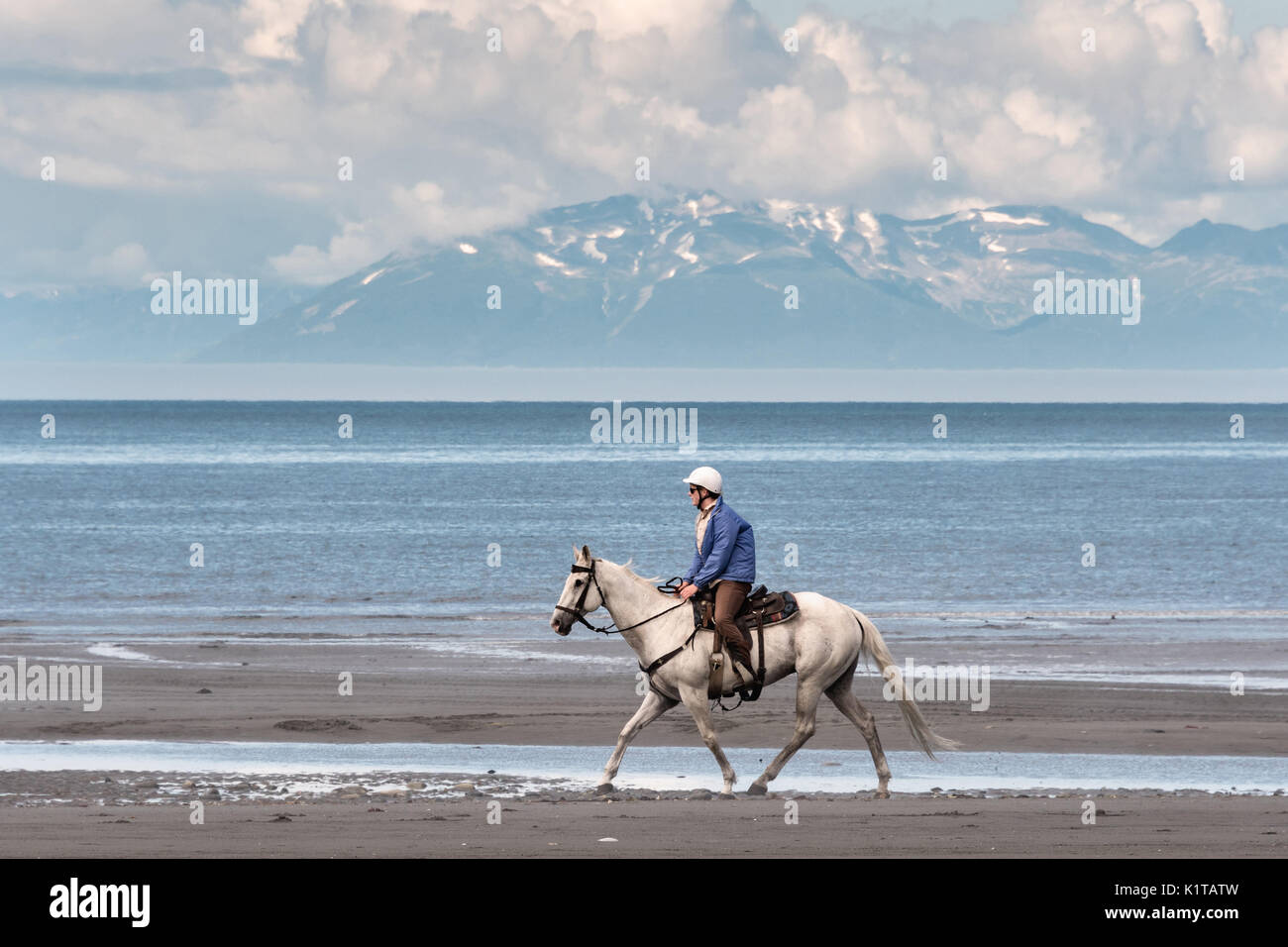 A woman rides her horse along the Cook Inlet past the Chigmit Mountains at Anchor Point, Alaska. - Stock Image