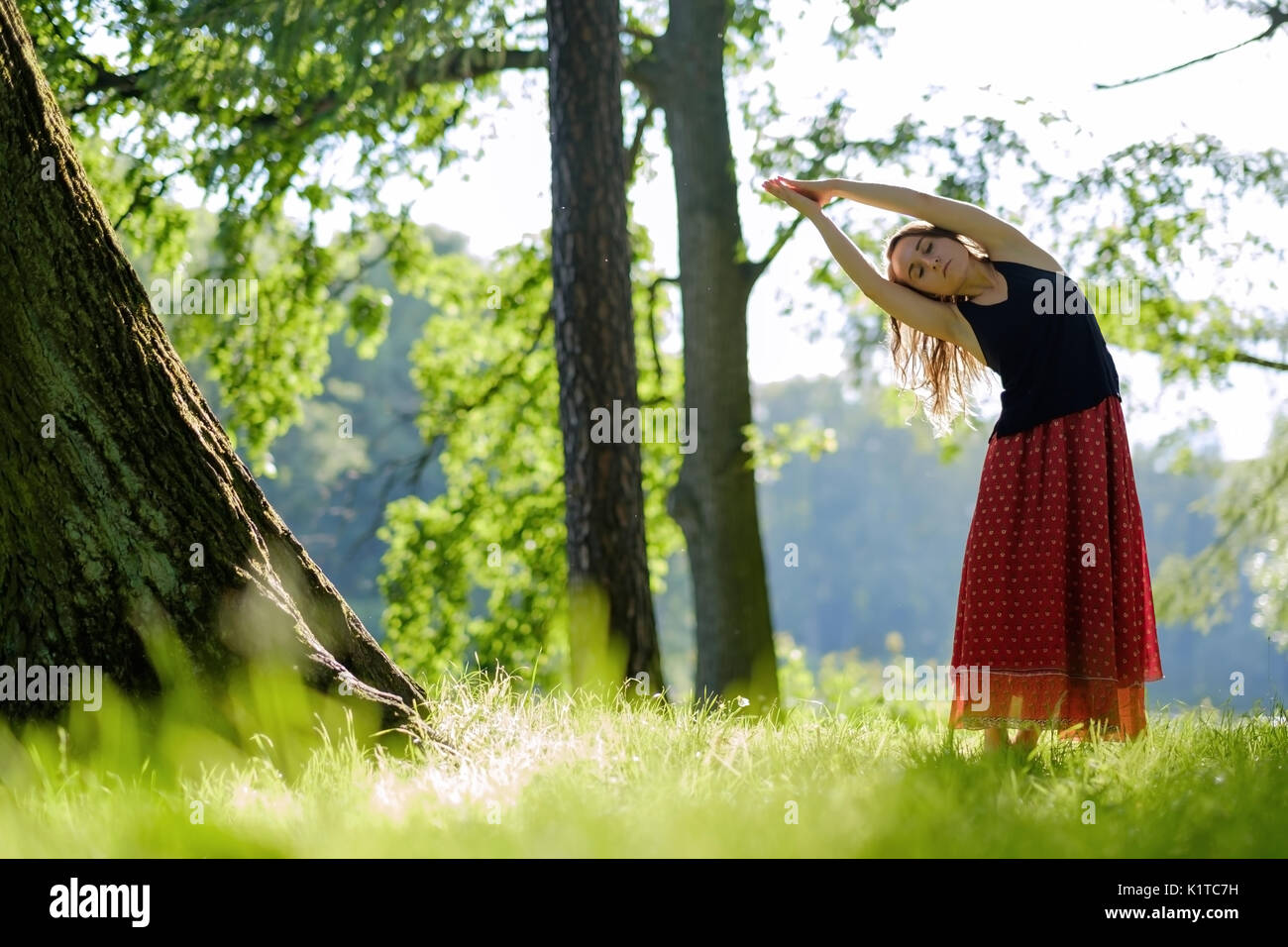 Attractive young female in red skirt is practicing yoga and doing asana in the morning. - Stock Image