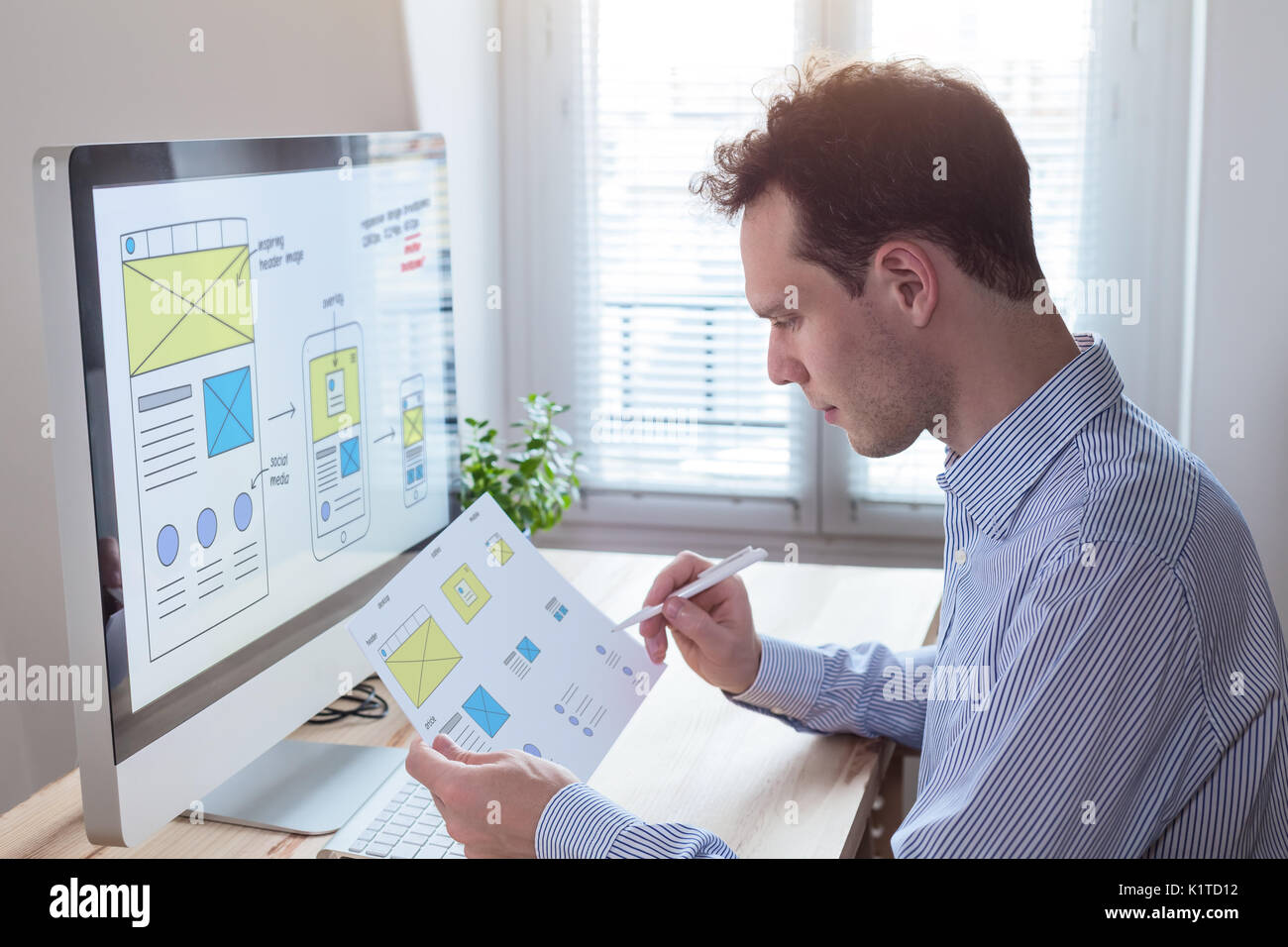 Website UI/UX front end designer reading client specification document and sketching wireframe layout design for responsive web content - Stock Image