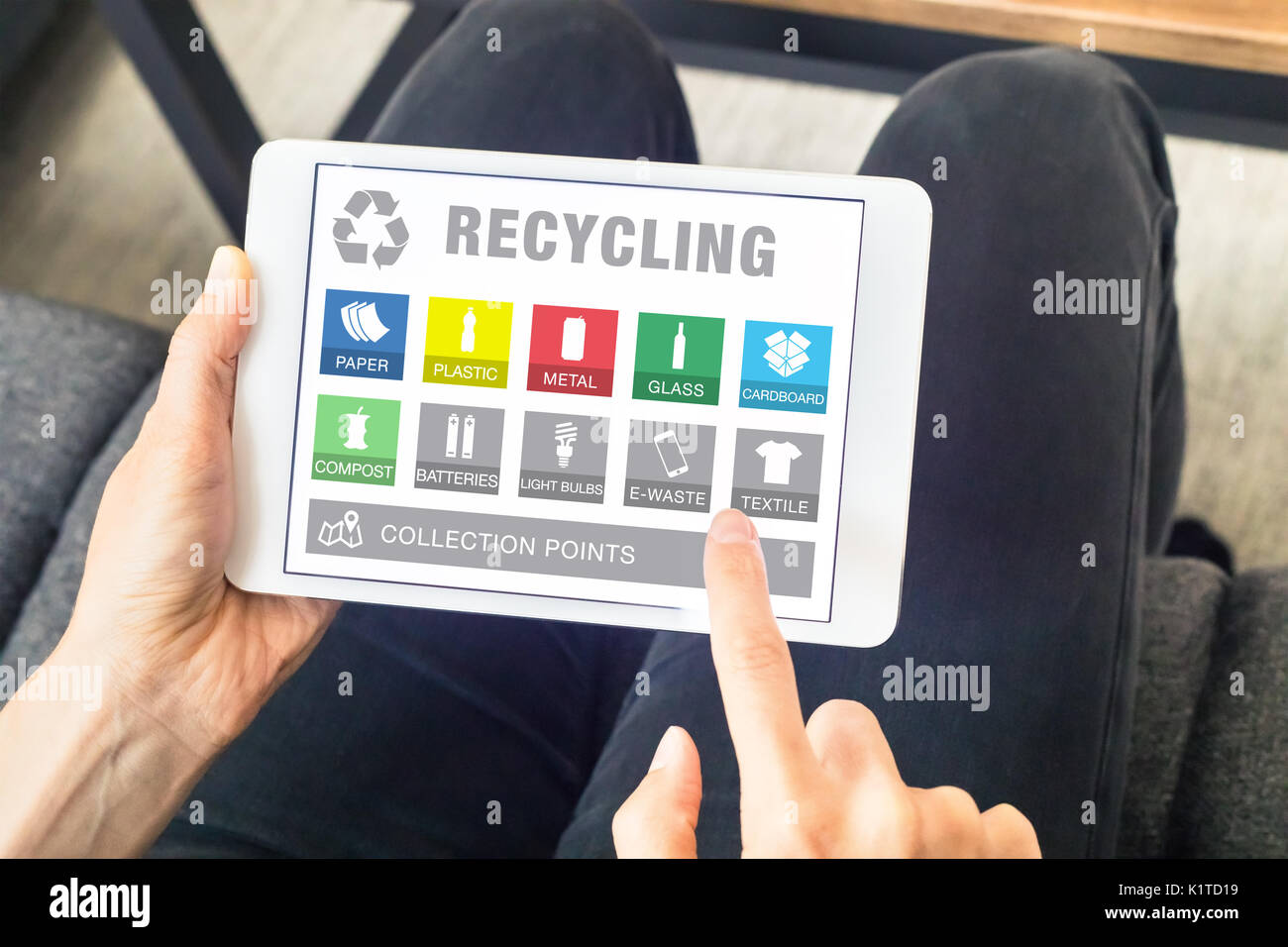 Person using digital tablet computer with app website for sorting recyclable material waste (icons of paper, plastic, metal can, glass bottle, e-waste - Stock Image