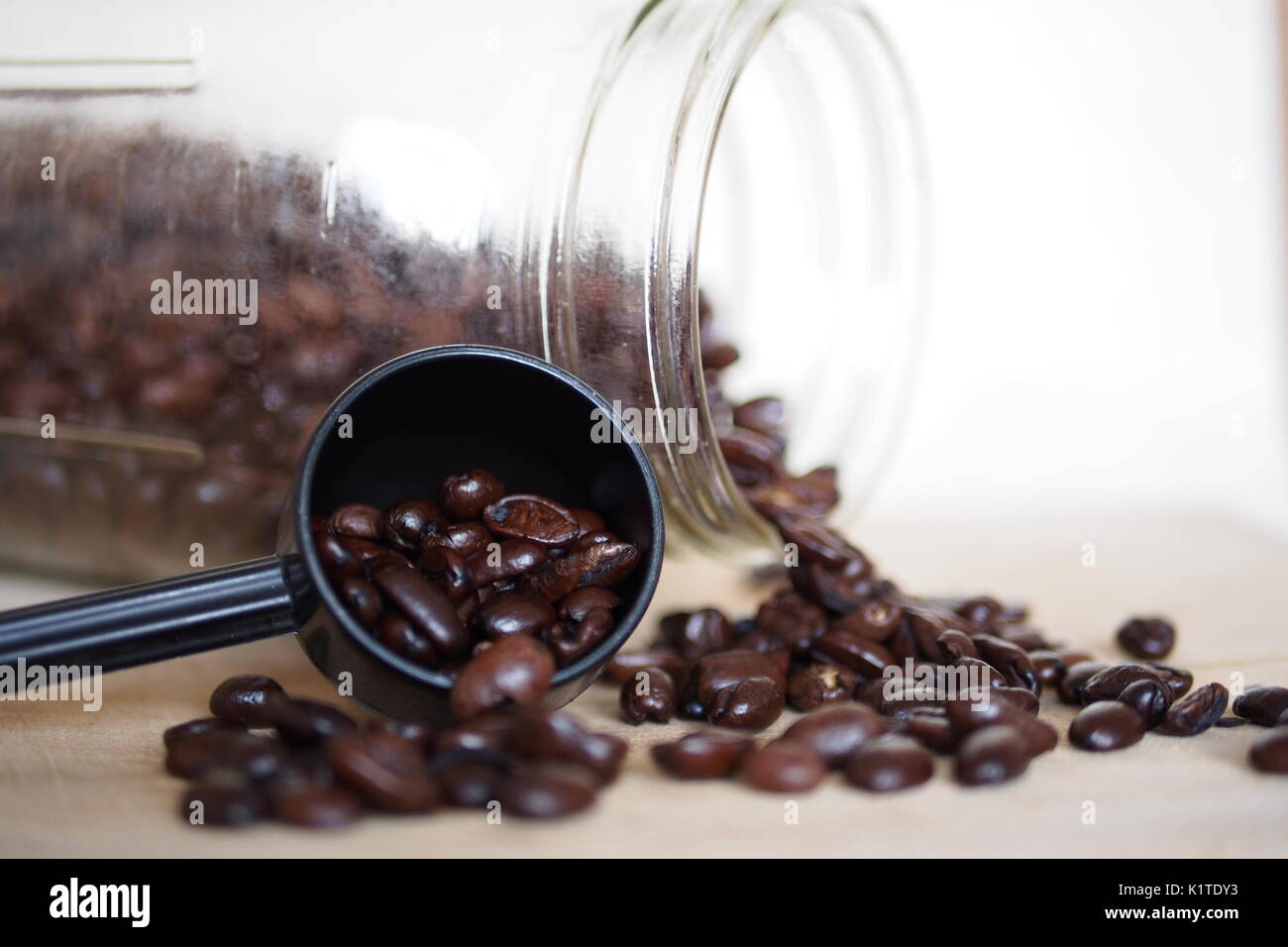Coffee beans spill from a glass jar and a measuring spoon onto a wooden cutting board. - Stock Image