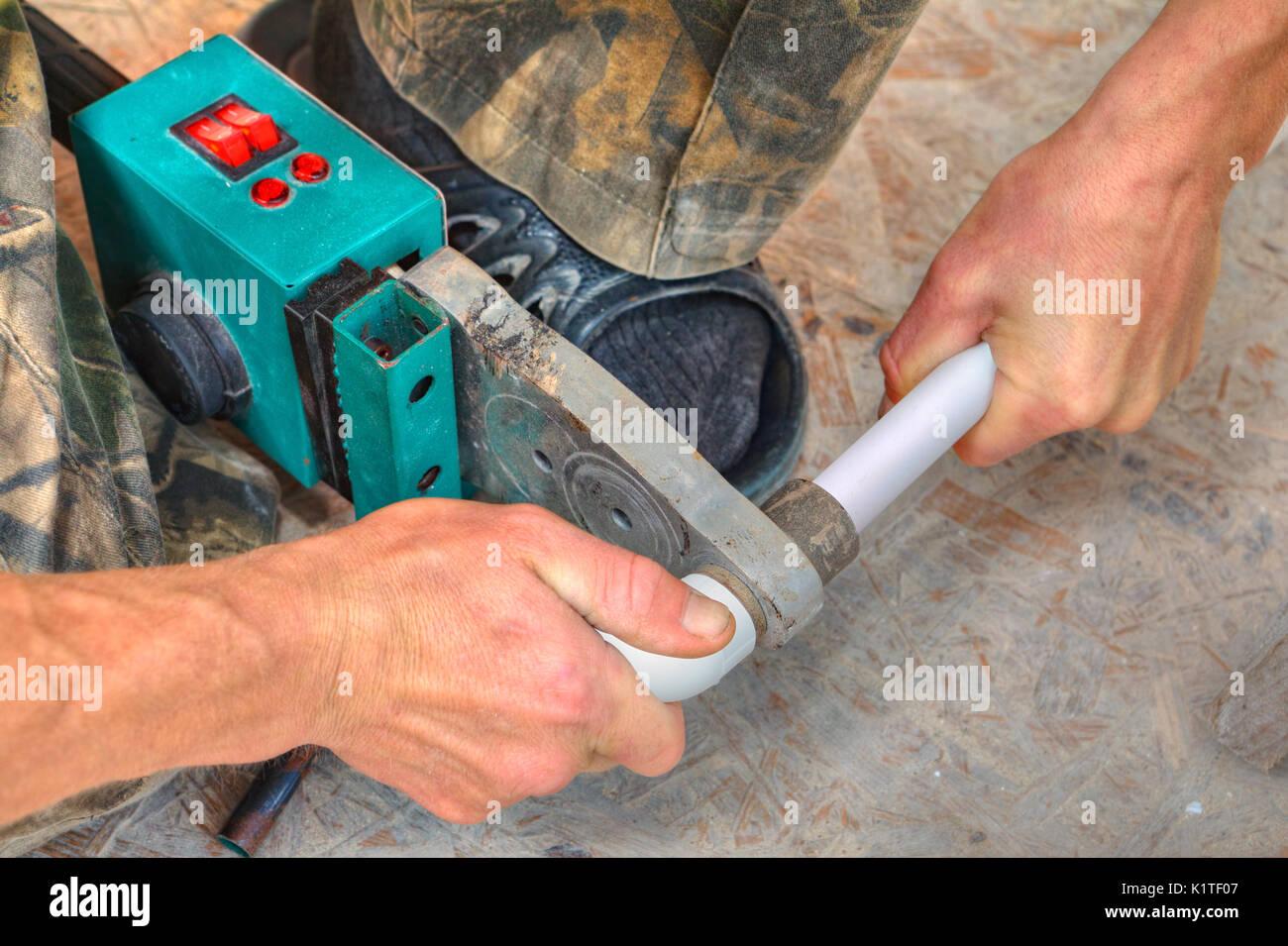 Plumber installing pipes in home, ppr plastic pipe hot melt welding