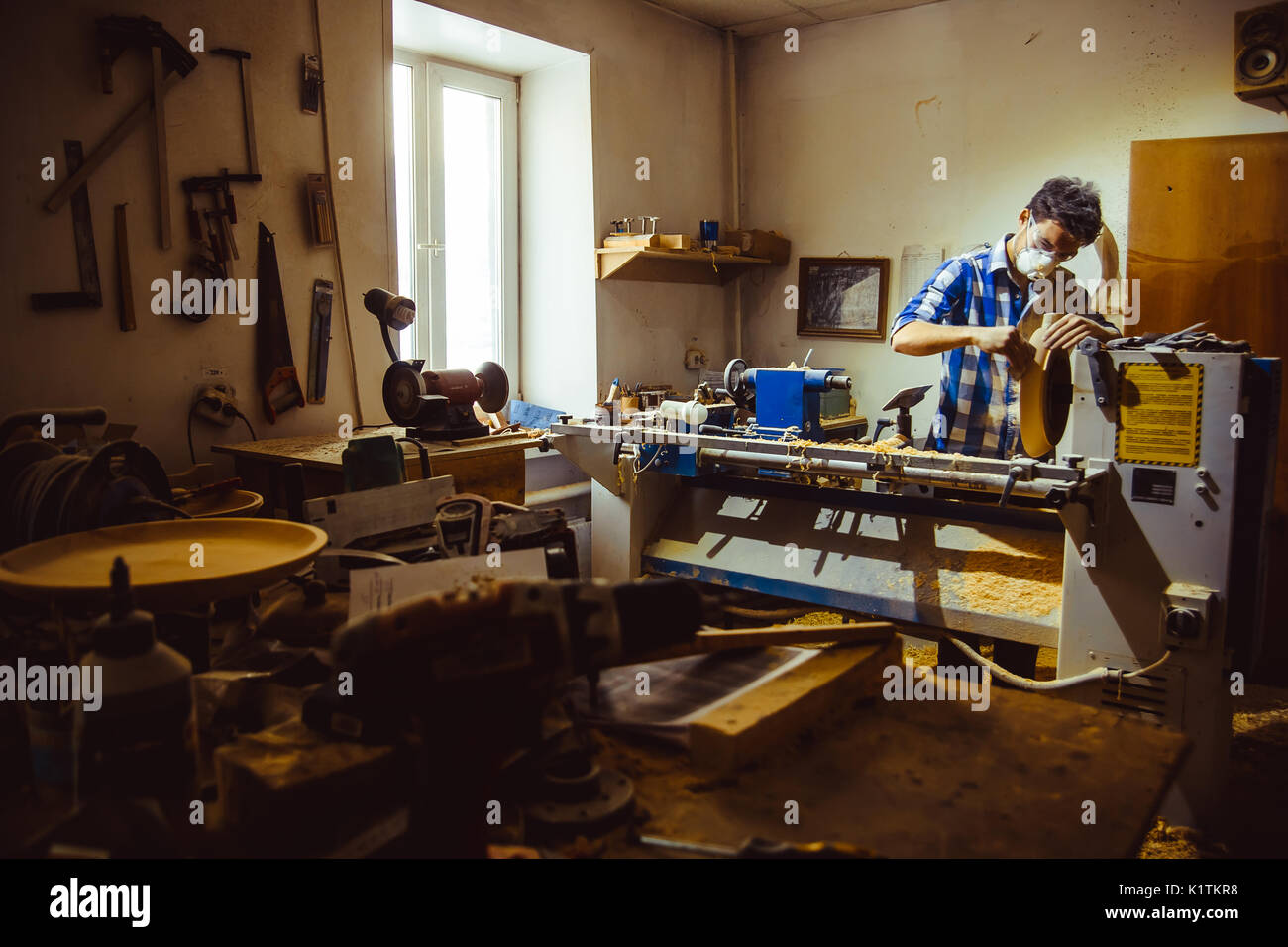 Leather crafting tools on working desk with the scratches. Blurred background of leather workshop. Copy space. - Stock Image