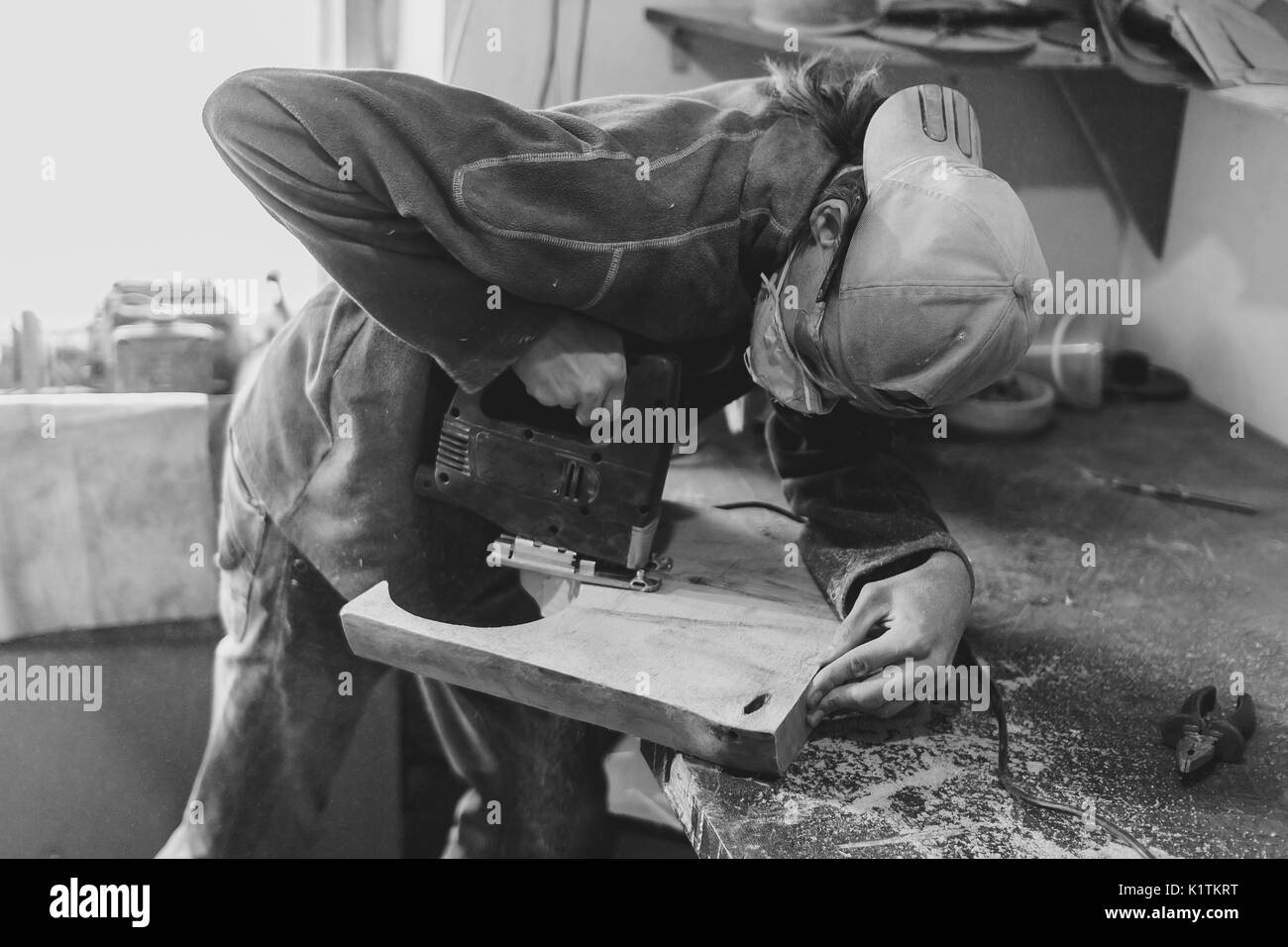 master saws a piece of wood in the workshop - Stock Image