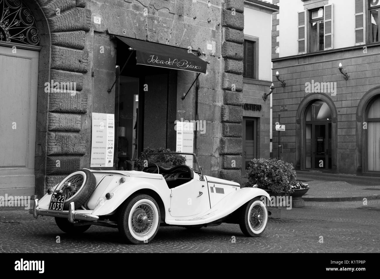 Vintage white car parked in front of a shop, at a public square in Orvieto, shot in Black and White. Car reflects the old character of Orvieto. - Stock Image