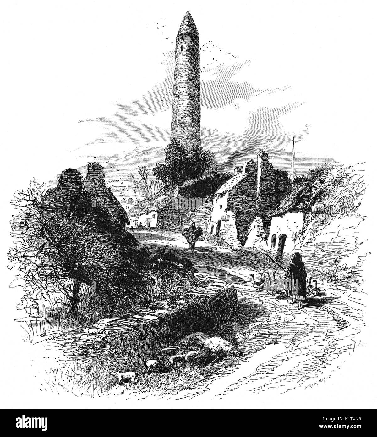 1870: Village life below the Round Tower built in the 5th Century monastic site instigated by St Patrick in Kilalla, County Mayo, Ireland - Stock Image