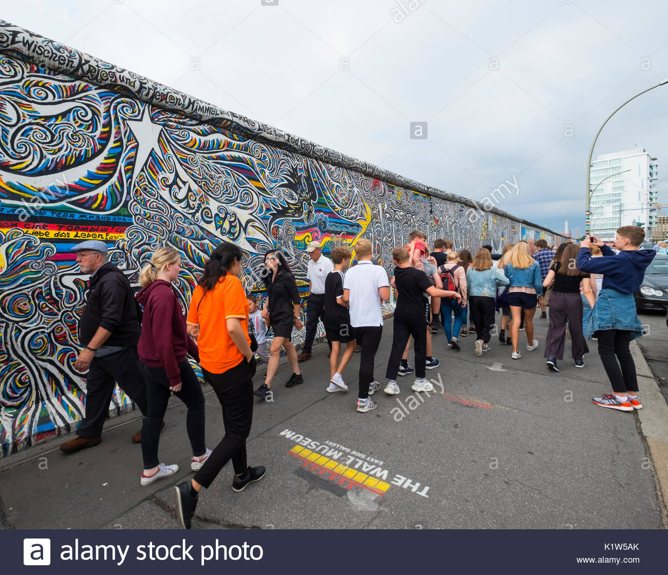 Many tourists walk past mural painted on original section of Berlin Wall at East Side gallery in Berlin, Germany - Stock Image