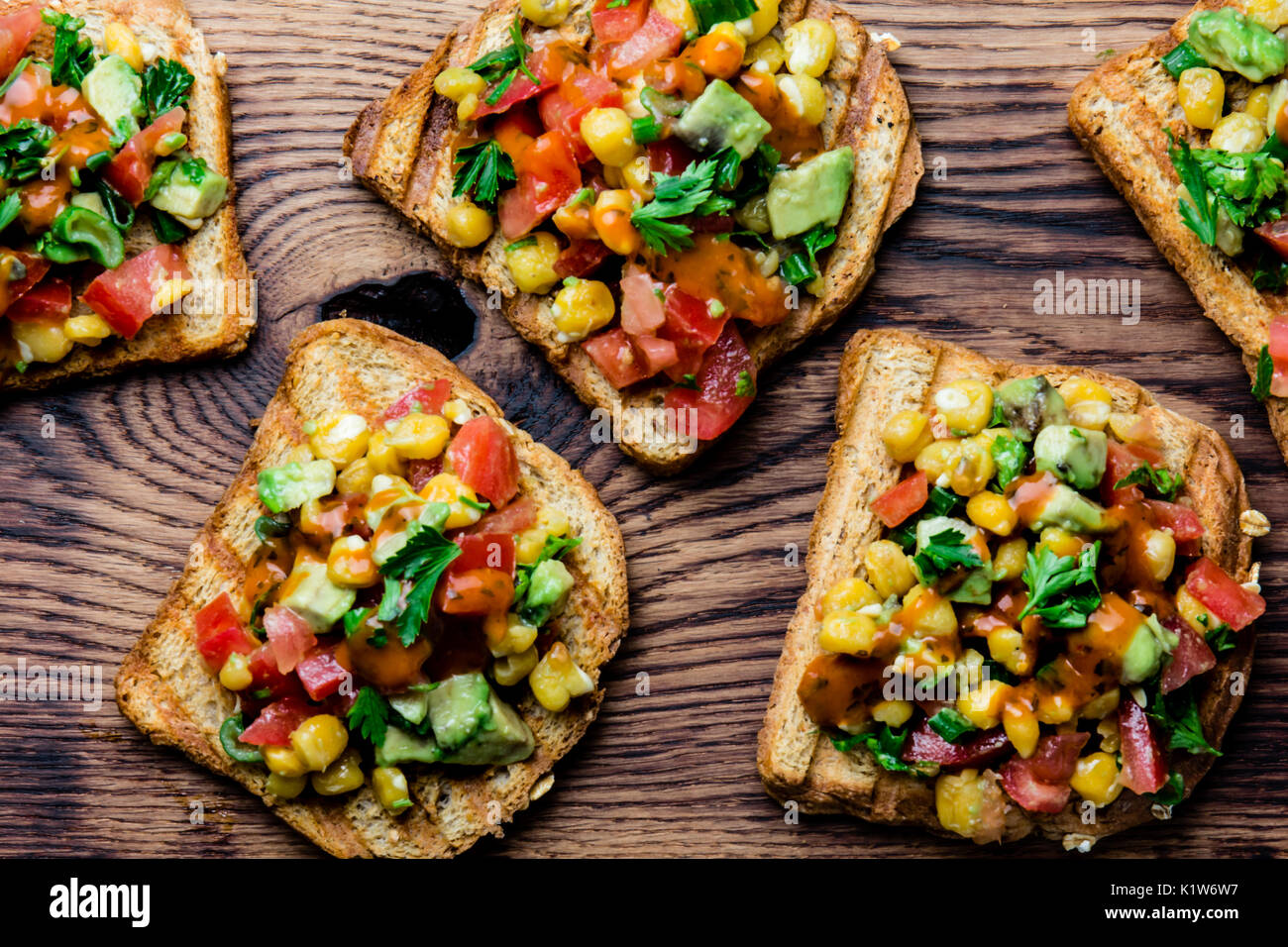Mexican latin american style open sandwiches vegetarian toasts with mexican latin american style open sandwiches vegetarian toasts with maize avocado tomatoes on wooden board rustic wooden blue background top view forumfinder Gallery
