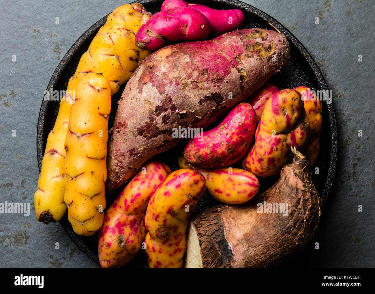 Peruvian raw ingredients for cooking - yuca, colored sweet potatoes and camote batata. Top view. - Stock Image