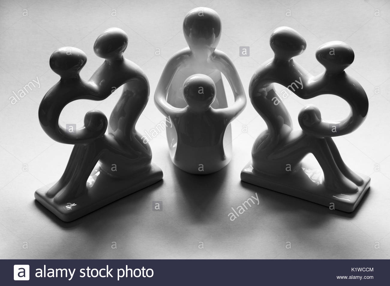 Family ties. Figurines arranged to represent Man the Father, Woman the Mother, the Girl and Boy their offspring. - Stock Image