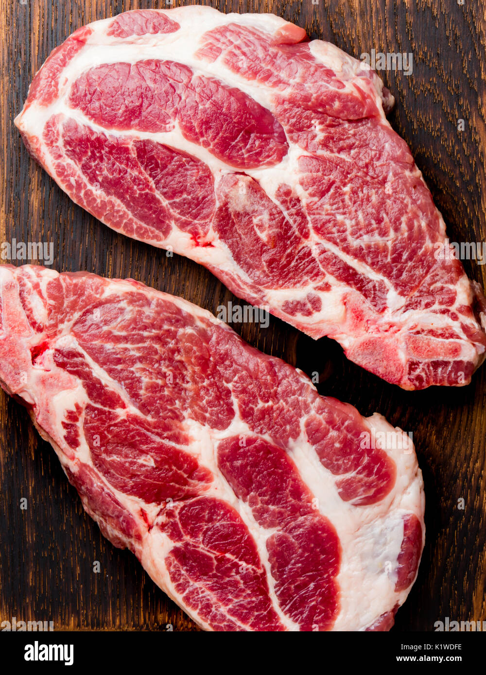 Raw pork cutlet chop for grill BBQ with herbs on wooden board, slate background, top view, copy spaces. - Stock Image