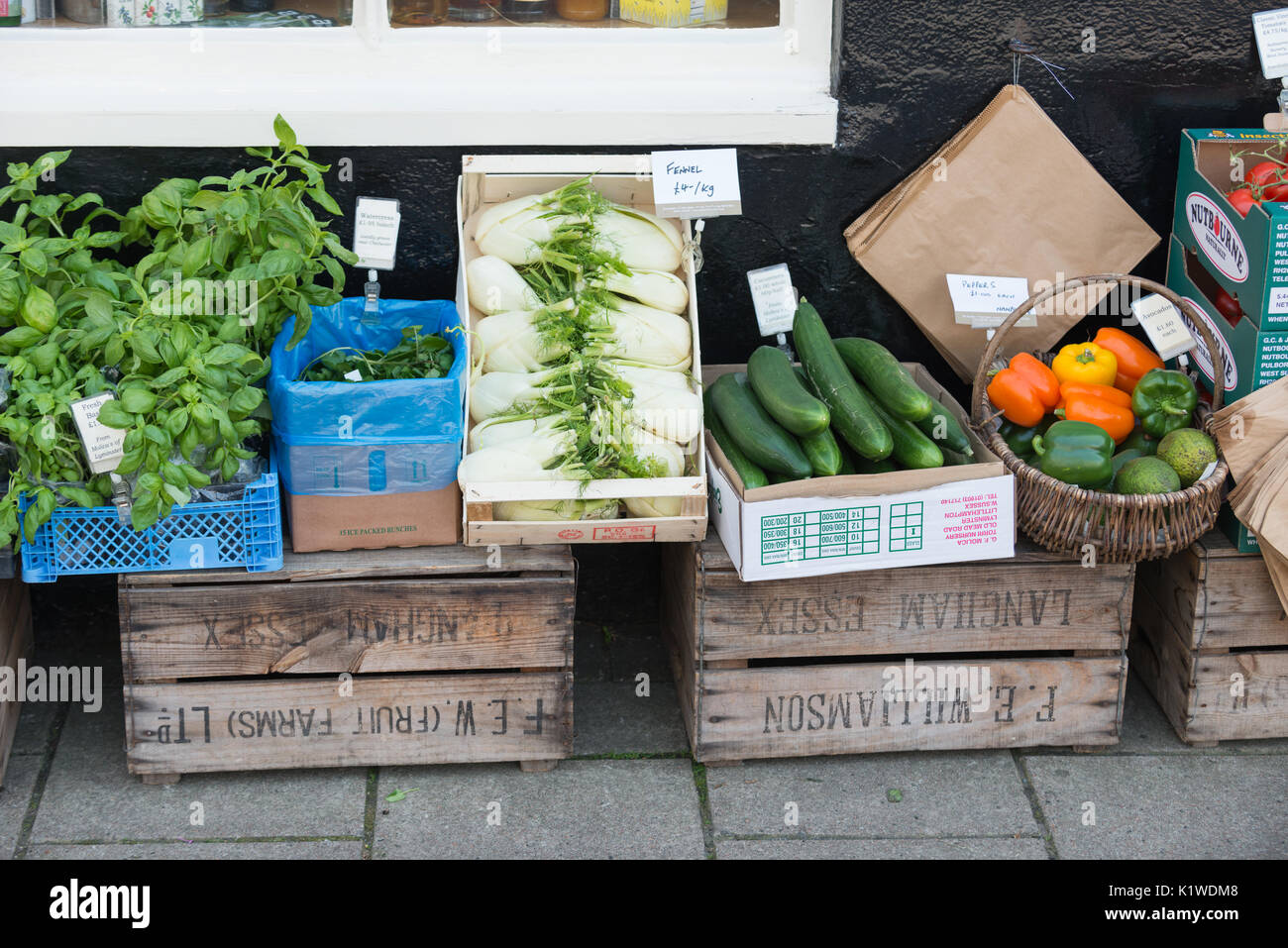 Boxes of fresh vegetables for sale outside a delicatessen in Arundel, West Sussex, England. - Stock Image