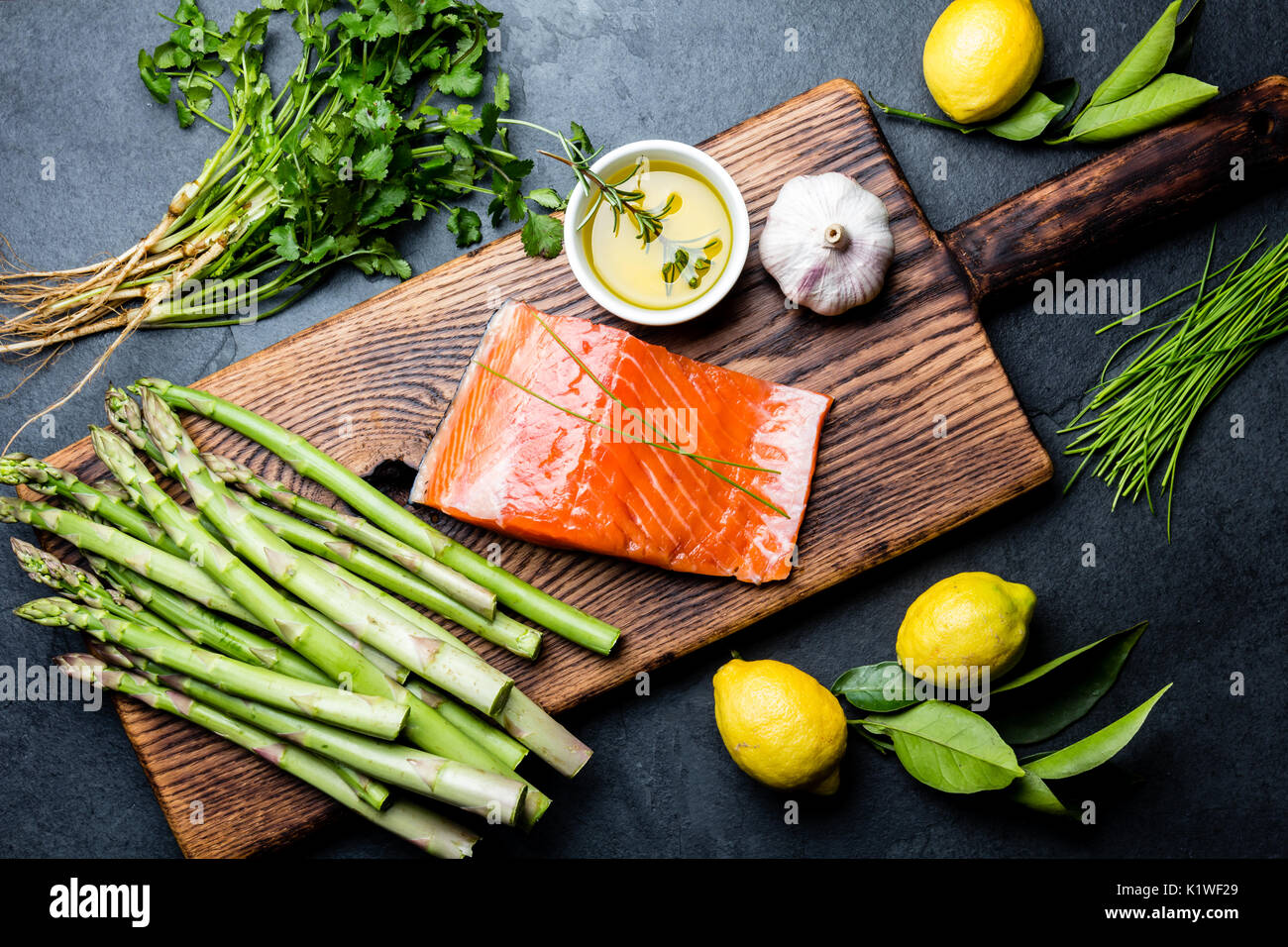 Ingredients for cooking. Raw salmon fillet, asparagus and herbs on wooden board. Food cooking background with copy space. Top view - Stock Image