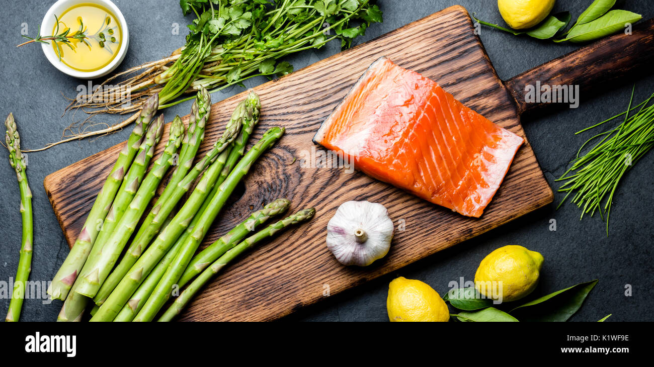 Ingredients for cooking. Raw salmon fillet, asparagus and herbs on wooden board. Food cooking background with copy Stock Photo
