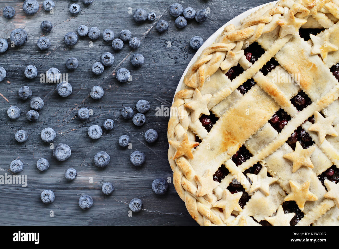 Top view of a blueberry pie with lattice and stars crust and fresh berries scattered across a painted textured wooden background. - Stock Image
