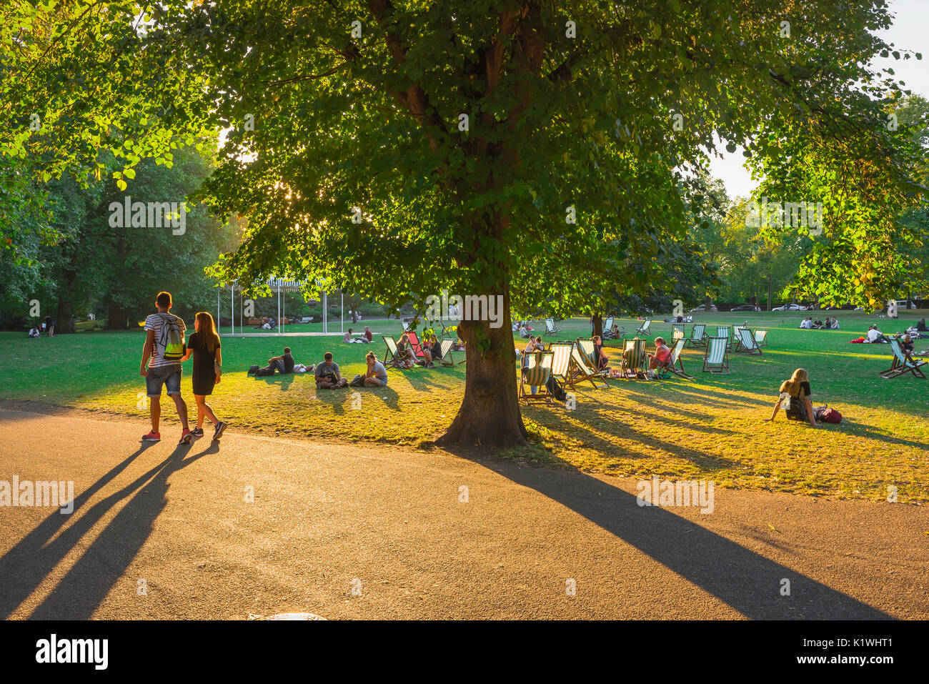 London park summer couple, people relax and socialise in St James's Park on a summer evening, London, UK. - Stock Image