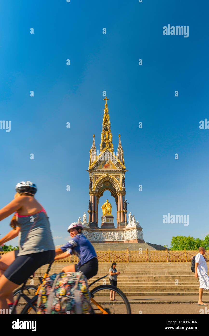 London summer cycling, on a summer afternoon two women tourists cycle past the Albert Memorial, London, UK - Stock Image