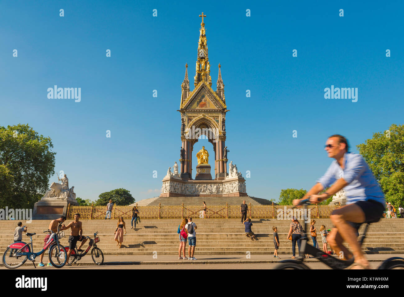 London summer cycling, on a summer afternoon tourists on bikes visit the Albert Memorial at the entrance to Kensington Gardens,London,UK - Stock Image