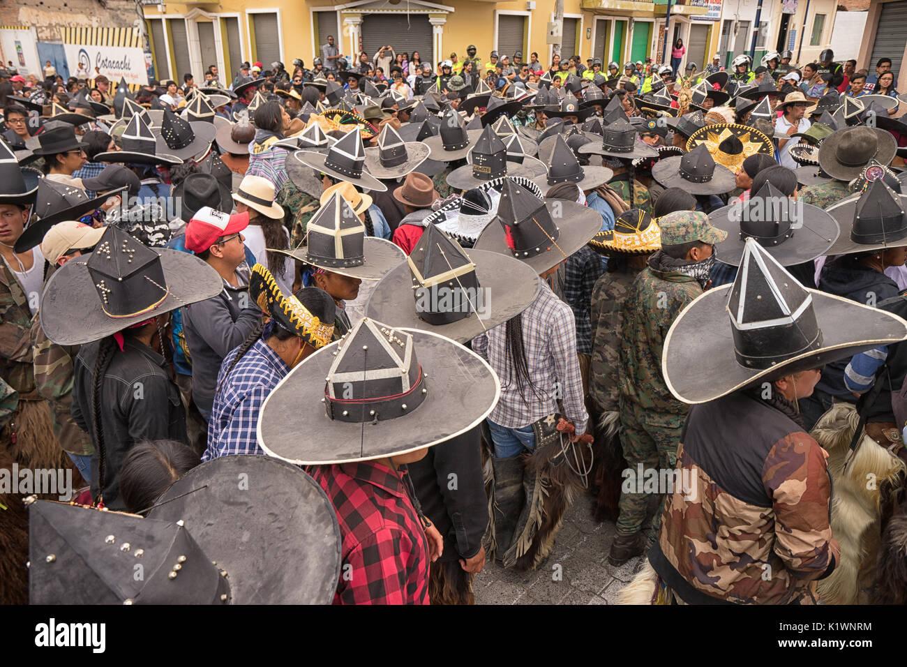 June 24, 2017 Cotacachi, Ecuador: street filled with dancing indigenous kichwa men at the Inti Raymi parade at summer solstice - Stock Image