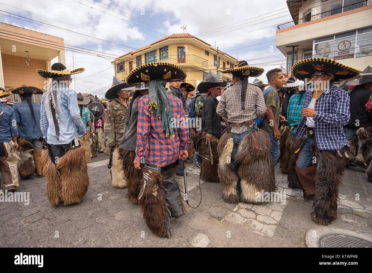 June 24, 2017 Cotacachi, Ecuador: dancing indigenous kichwa men at the Inti Raymi parade at summer solstice - Stock Image