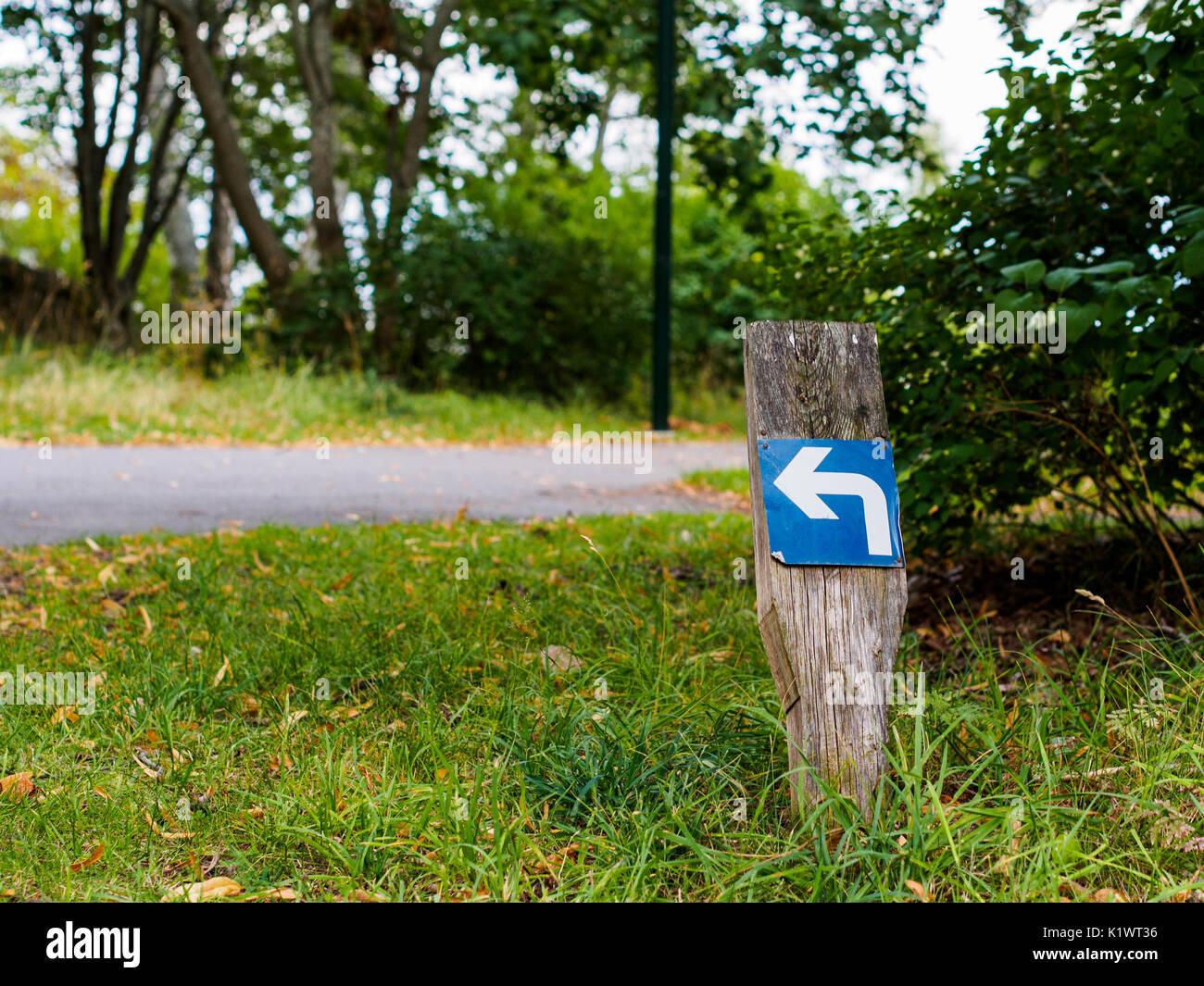Turn left arrow sign on a stick Stock Photo