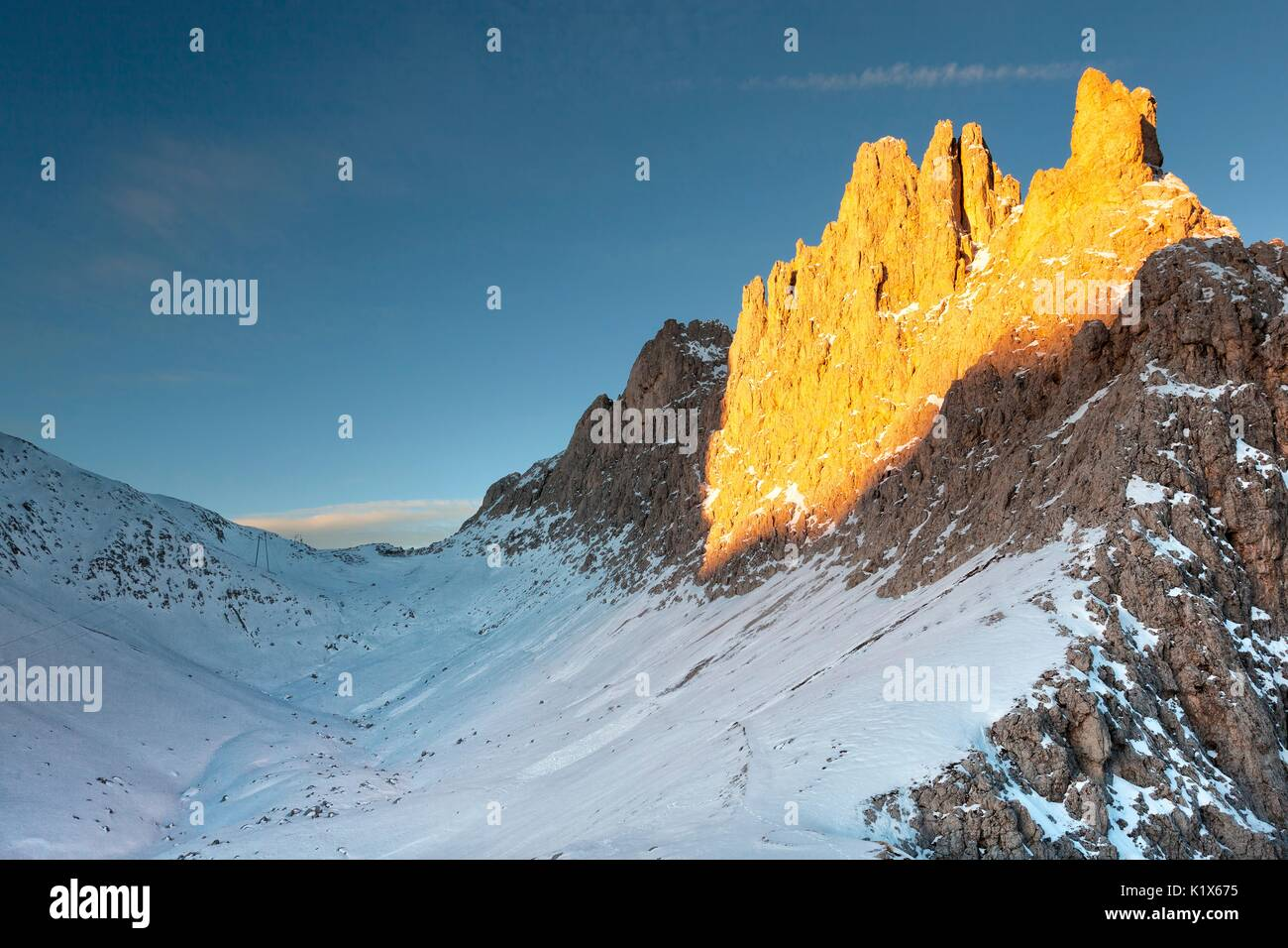 Santnerpass and Croda of King Laurin (Croda di Re Laurino) in a sunlit morning in early winter. Snow covers the entire path to the Santner pass, Rosen - Stock Image