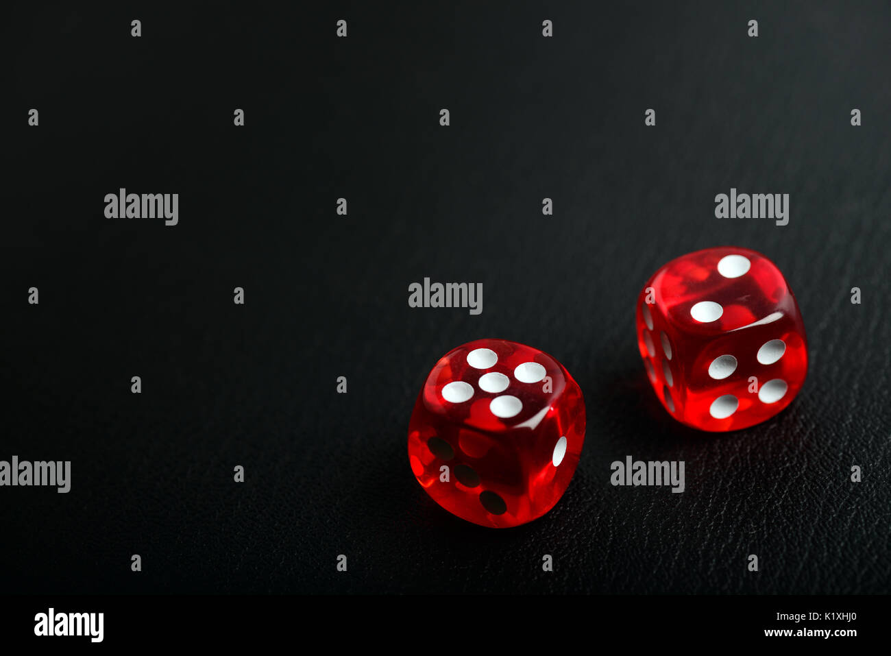 Two red casino poker dice counting seven on a bleack leather background with copy spce for your text - Stock Image