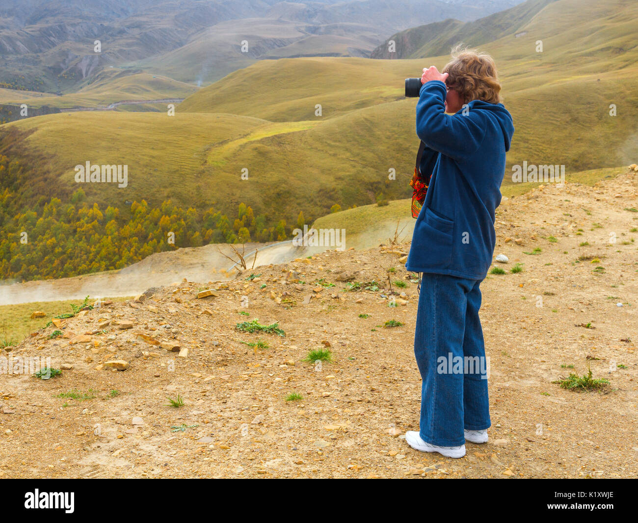 Nice looking pretty blondy caucasian happy successful girl with camera staying within the mountain landscape shooting mountain landscape. - Stock Image