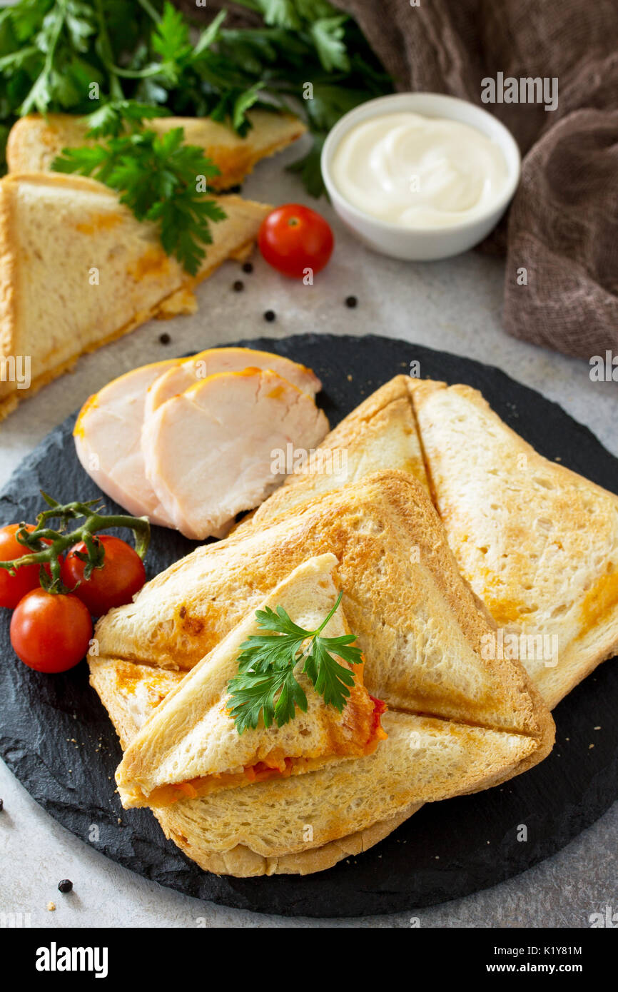 Pressed and toasted double sandwich with chicken, Korean carrots, cheese and tomatoes on a gray stone or slate. Stock Photo