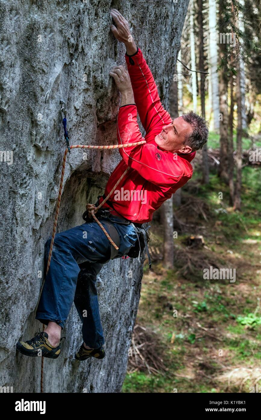 Free climbing, rock climbing in natural cliff. Climber in action on a rock path equipped. Gares, Dolomites, Veneto, Stock Photo