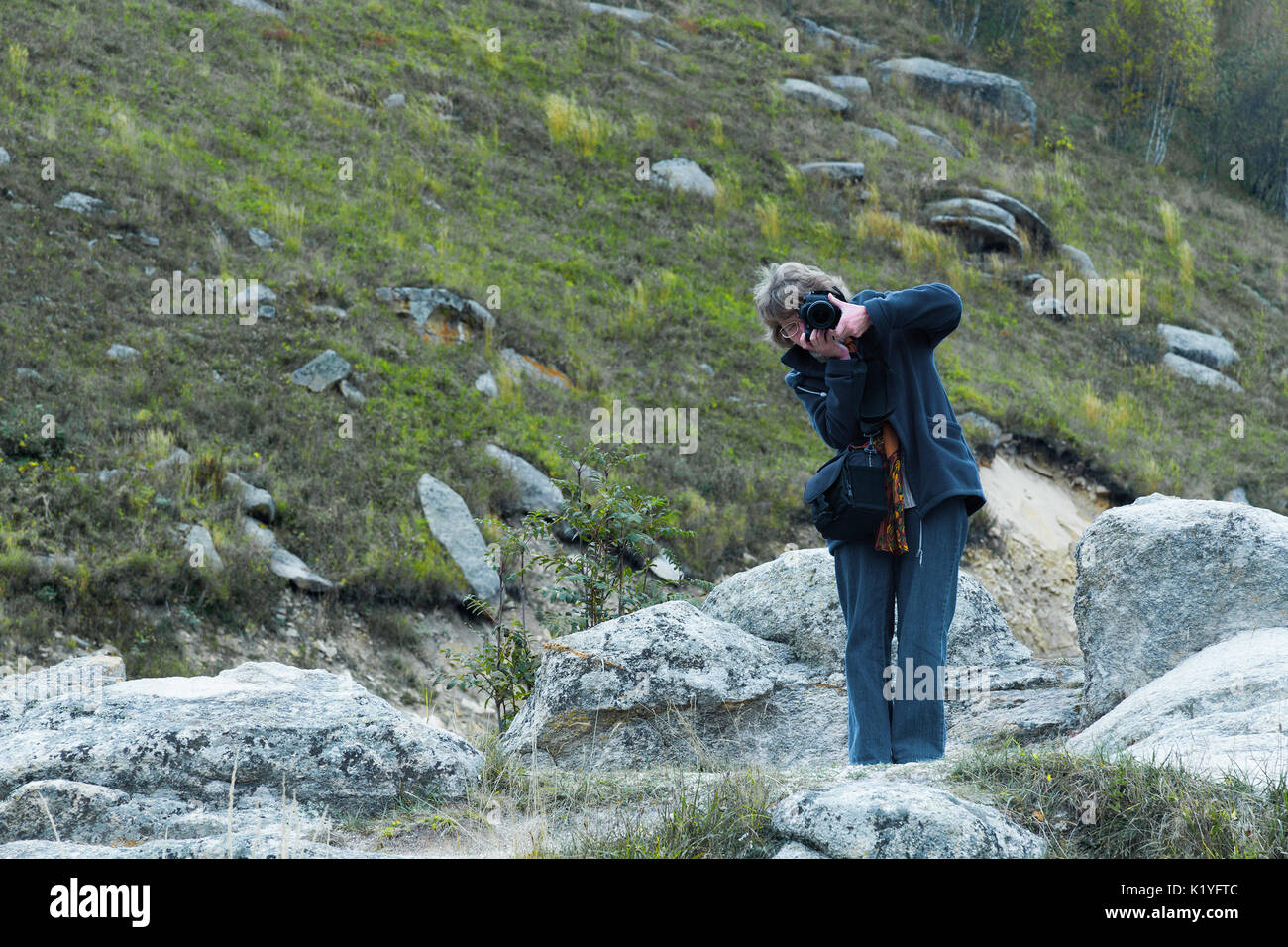 Nice looking pretty blondy caucasian happy successful girl with camera staying within the mountain landscape shooting somebody. - Stock Image
