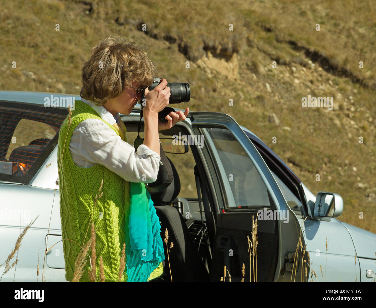 Nice looking pretty blondy caucasian happy successful girl with camera staying near her car within the mountain landscape shooting nature. - Stock Image