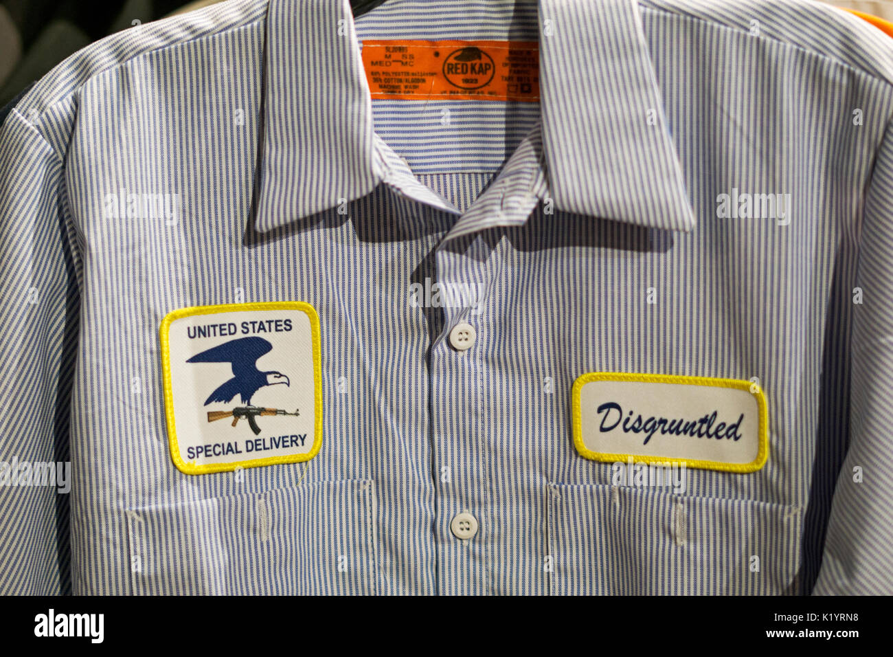A gag gift of a disgruntled postman's shirt for sale at the Halloween Adventure costume shopin Greenwich Village, New York City - Stock Image