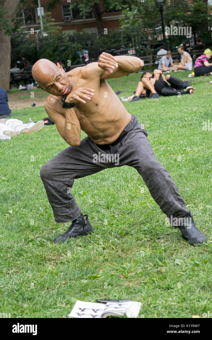 A fit shirtless 67 year old man practices kung fu moves outdoors in Washington Square Park in Greenwich Village, New York City - Stock Image