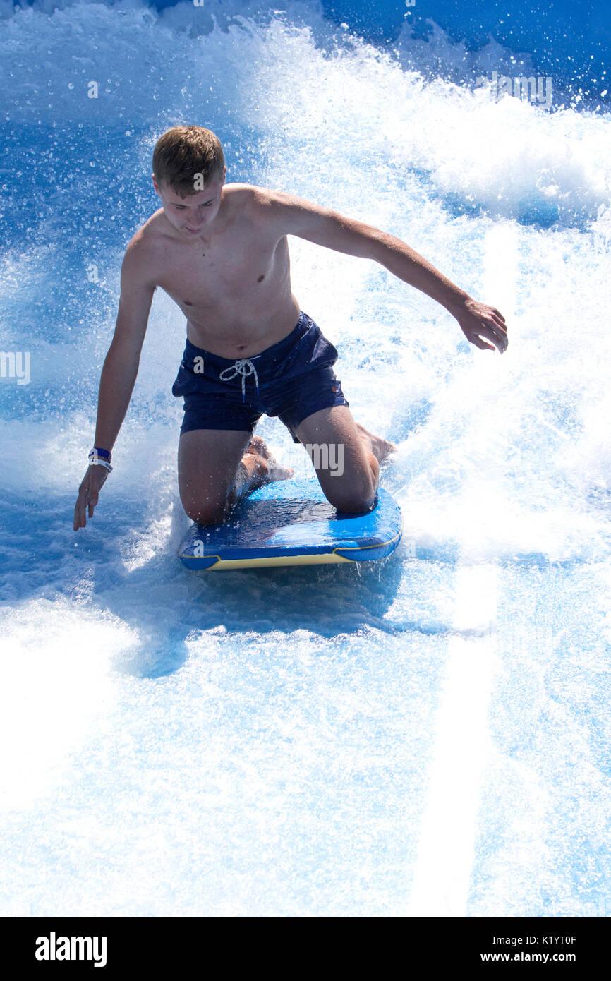 Young man on a Royal Caribbean Navigator of the Seas cruise ship Flow Rider surf simulator - Stock Image