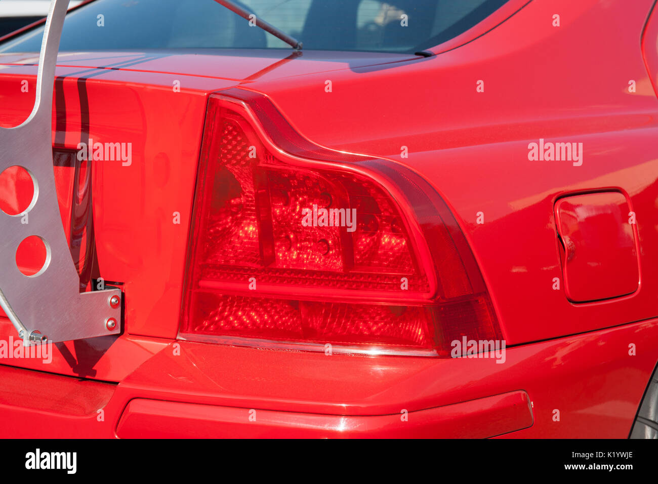 Red rear light of a red sports car. White metal support of a back spoiler. Beautiful automotive technology. Stylish design. - Stock Image