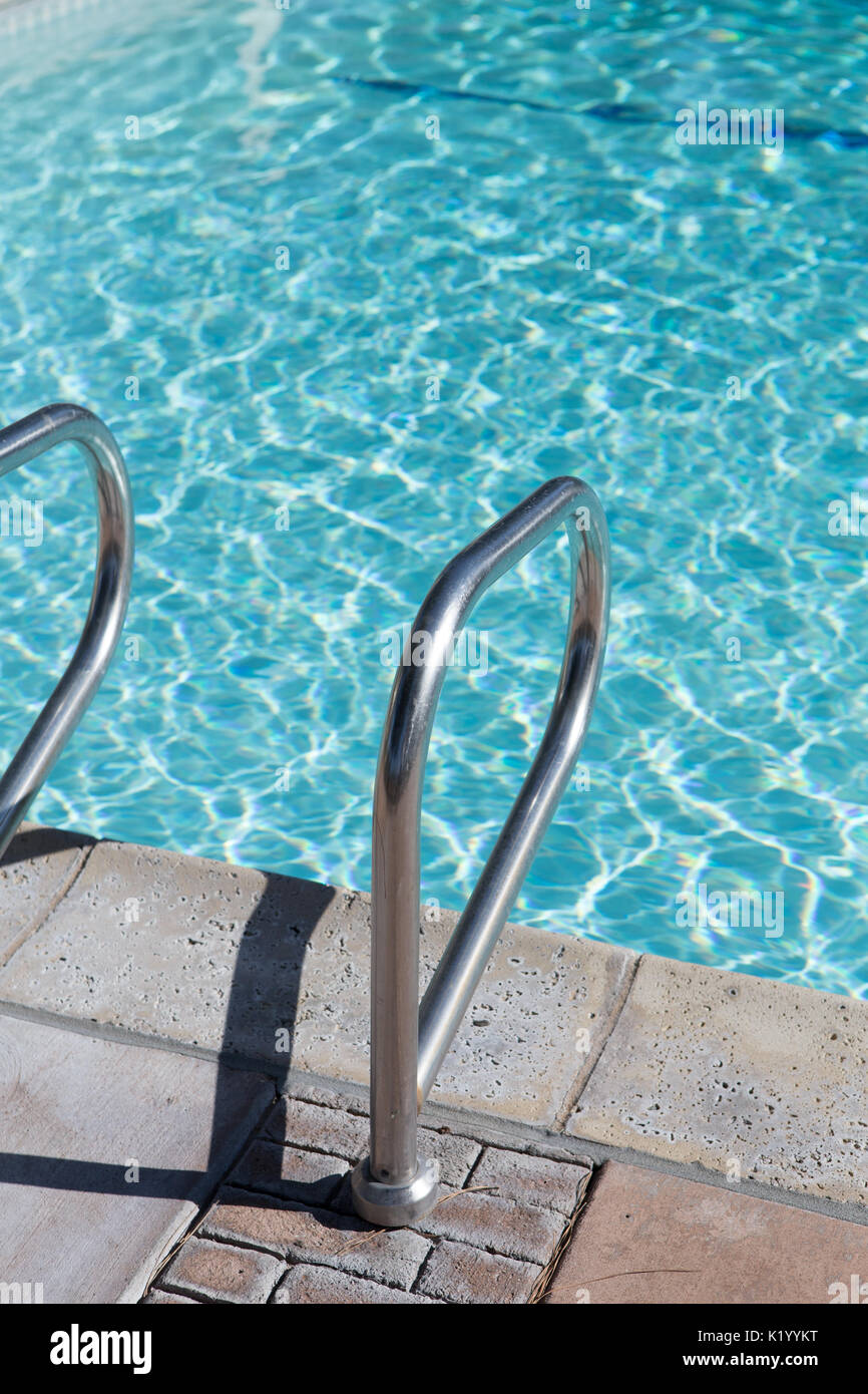 Sunlight glistening off the crystal clear water of a beautiful swimming pool.A view of pool steps enticing the viewer into the cool water on a hot day - Stock Image