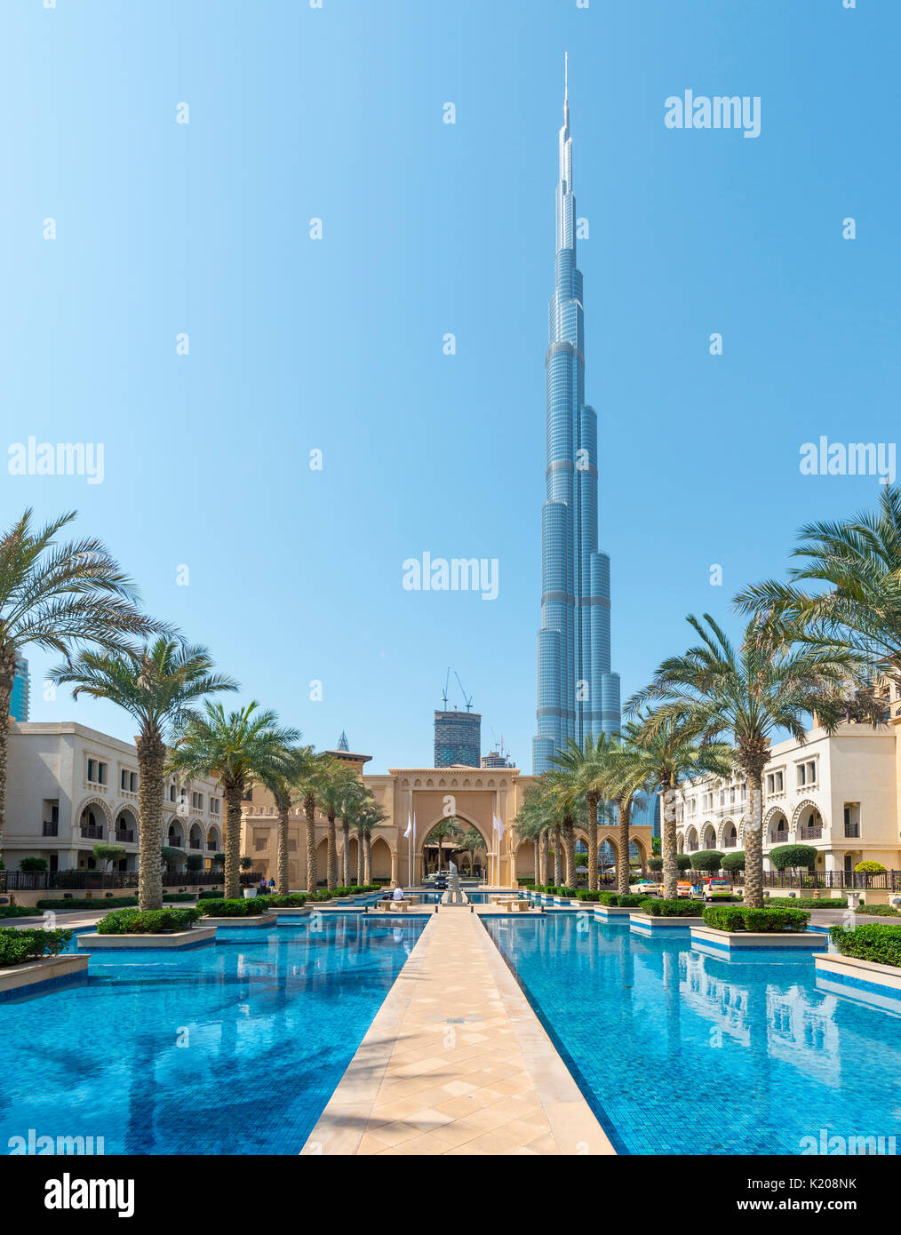 Palace city hotel, palm trees and fountains, at back Burj Khalifa, Dubai, Emirate Dubai, United Arab Emirates - Stock Image